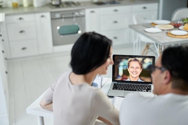 Glücklicher eheberater, der seine kunden anlächelt, die video-chat-app verwendet und während der sperrung hilfe leistet. online-beratungskonzept. fokus auf laptop-bildschirm