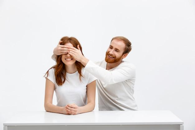 Glücklicher ehemann bedeckt frauaugen mit handflächen