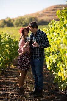 Glücklicher ehemann und ehefrau in einem weinberg auf dem land mit gläsern weißwein.