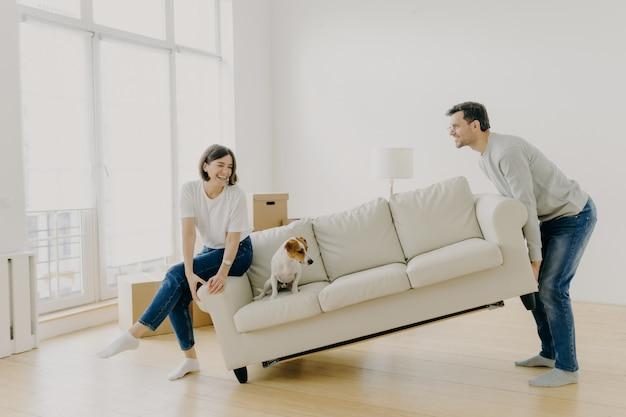 Glücklicher ehemann und ehefrau setzen sofa in wohnzimmer, richten ihr erstes zuhause ein, helfen sich gegenseitig bei der renovierung