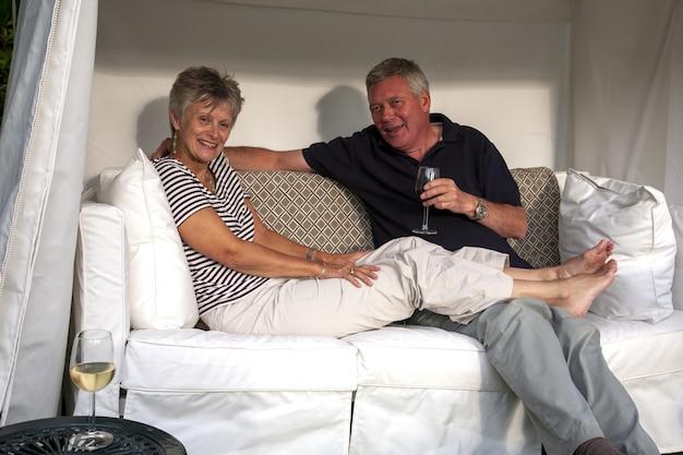 Glücklicher ehemann und ehefrau sitzen zusammen auf dem sofa und lächeln