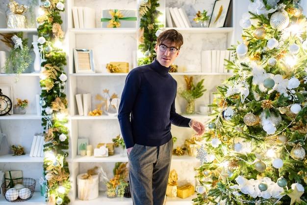 Glücklicher eleganter geschäftsmann, der für kamera nahe weihnachtsbaum im gemütlichen raum mit winterurlaubdekorationen aufwirft