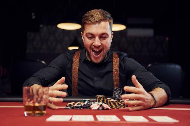 Glücklicher eleganter junger mann sitzt im kasino und feiert seinen sieg im pokerspiel