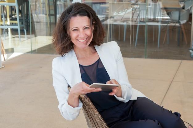 Glücklicher eleganter weiblicher tourist, der tablette verwendet