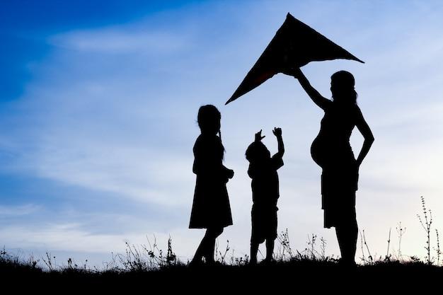 Glücklicher elternteil mit kindern, die auf natursommerschattenbild spielen
