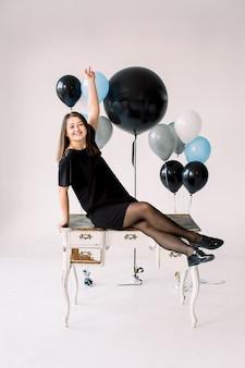 Glücklicher emotionaler glamour lächelnde junge frau im schwarzen kleid und in den schuhen mit geburtstagsfeiertagsballons, die auf weißem hölzernen weinlese-tisch innen sitzen