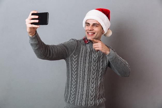 Glücklicher emotionaler mann, der weihnachtshut trägt, machen selfie per telefon.