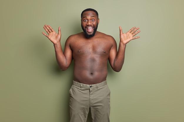 Glücklicher emotionaler mann mit dunkler haut hebt handflächen und reagiert glücklich auf unerwartete überraschungslächeln, die weitgehend hemdlos stehen
