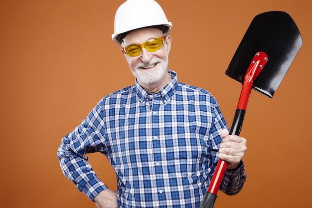 Glücklicher energetischer älterer männlicher bagger mit grauer stoppeln, die schaufel zum graben, heben und bewegen von schüttgütern halten, mit positivem selbstbewusstem lächeln. baumaschinen, werkzeuge und instrumente