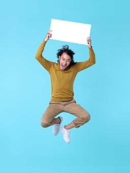 Glücklicher energetischer junger asiatischer mann, der in der luft springt und leere sprechblasen auf blauem hintergrund hält.