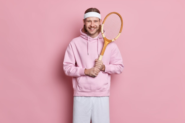 Glücklicher energetischer sportlicher mann hält tennisschläger genießt das spielen des lieblingsspiels hat aktives leben trägt stirnband-sweatshirt und shorts genießt großen tag zum spielen.