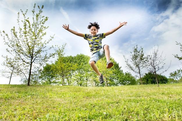 Glücklicher energiejunge, der hoch in die luft springt