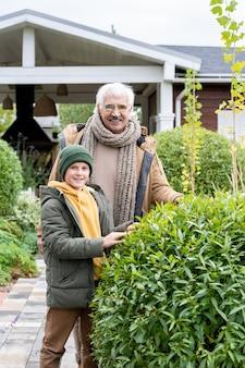 Glücklicher enkel und großvater in warmer freizeitkleidung, die vor der kamera im garten neben ihrem landhaus am grünen busch stehen