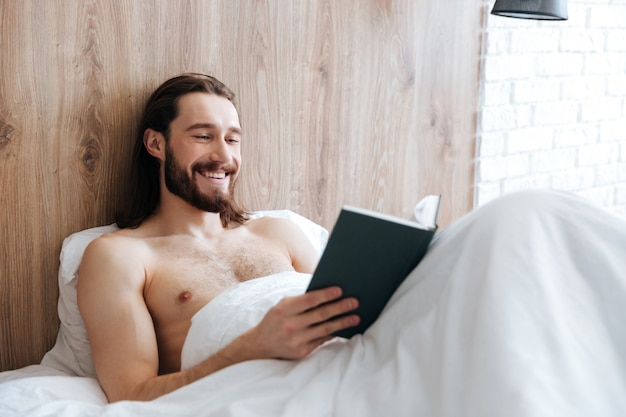 Glücklicher entspannter junger mann, der buch im bett liegt und liest