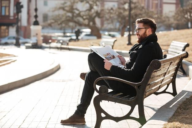 Glücklicher entspannter junger mann, der zeitung auf der bank draußen liest