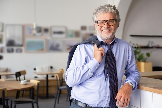 Glücklicher entspannter reifer geschäftsmann, der im bürocafé steht, sich auf zähler stützt, jacke über schulter hält und kamera anlächelt