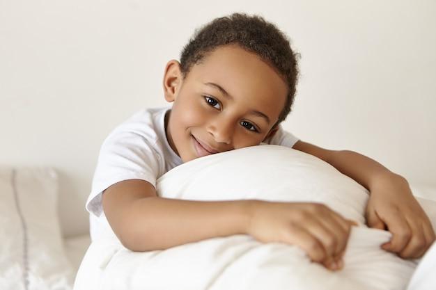 Glücklicher entzückender dunkelhäutiger junge afrikanischen ursprungs, der am wochenende nach dem erwachen im bett entspannt