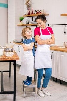 Glücklicher entzückender junge und seine mutter in den weißen schürzen, die arme auf der brust kreuzen, während sie einander in der küche betrachten