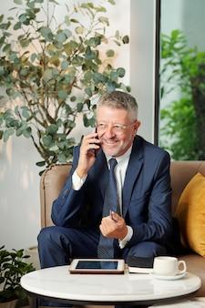 Glücklicher erfolgreicher älterer unternehmer, der mit kollegen oder geschäftspartnern am telefon spricht