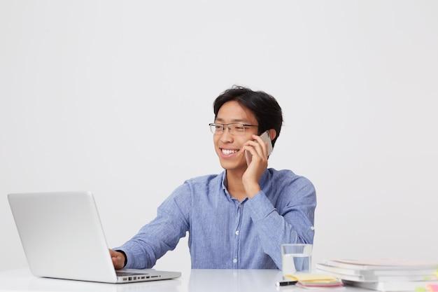 Glücklicher erfolgreicher asiatischer junger geschäftsmann in den gläsern und im blauen hemd, die auf handy sprechen, das mit laptop am tisch über weißer wand arbeitet