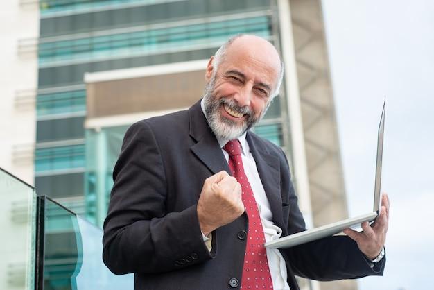 Glücklicher erfolgreicher fälliger unternehmensleiter mit laptop