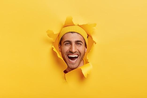 Glücklicher erfreuter mann mit zahnigem lächeln, trägt hut