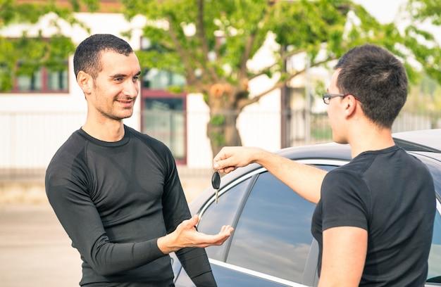 Glücklicher erfüllter junger mann, der autoschlüssel nach gebrauchtverkauf empfängt