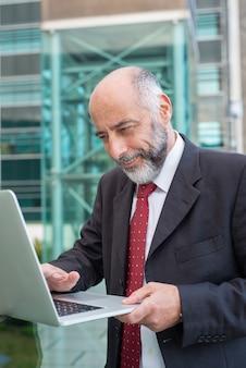 Glücklicher erfüllter reifer geschäftsmann mit aufpassendem inhalt des laptops