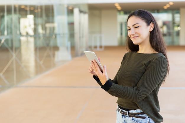 Glücklicher erfüllter weiblicher kunde, der e-mail auf tablette überprüft
