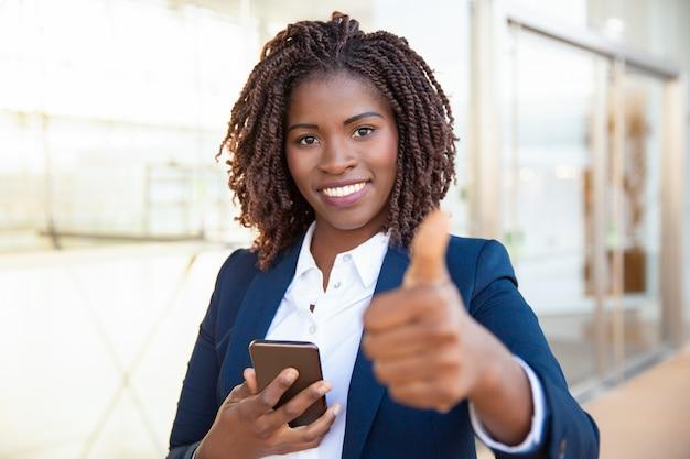 Glücklicher erfüllter weiblicher kunde, der mobiltelefon hält