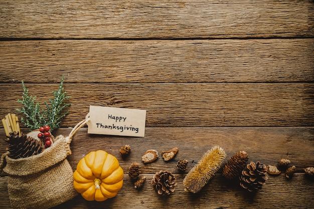 Glücklicher erntedankfesthintergrund mit kürbis und gruß etikettieren auf hölzerner tabelle