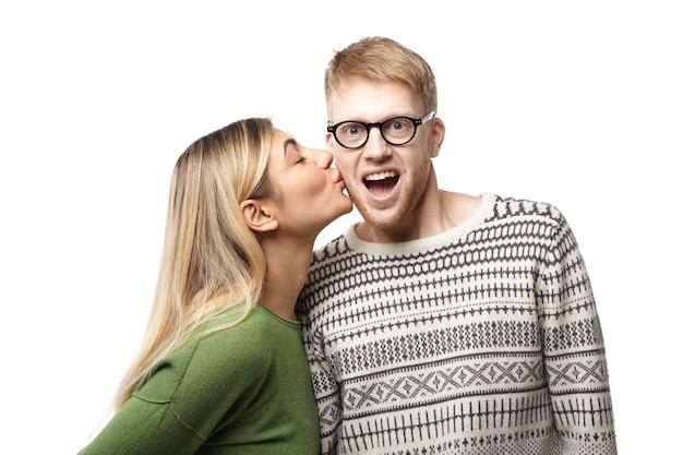 Glücklicher erstaunter junger geeky kerl mit bart, der brille und pullover trägt, öffnet aufgeregt mund, während er von attraktiver blonder frau auf wange geküsst wird. liebes- und romantikkonzept