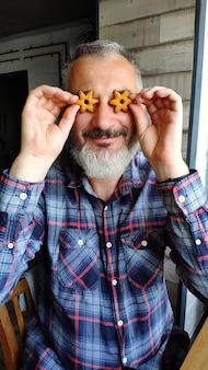 Glücklicher erwachsener bärtiger mann hält zwei plätzchen in form der sterne vor seinen augen, stellt gläser, ein spaßkonzept mit plätzchen dar
