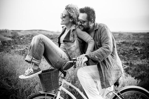 Glücklicher erwachsener kaukasier, paar, die spaß mit dem fahrrad in der freizeitbeschäftigung im freien haben