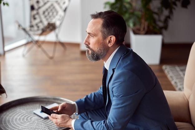 Glücklicher erwachsener mann arbeitet in einem modernen büro