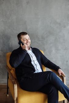 Glücklicher erwachsener mann, der auf einem sessel sitzt und drinnen telefoniert