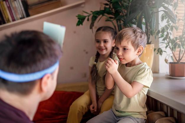 Glücklicher erwachsener vater, der brettspiel mit seinen zwei kindern im häuslichen innenraum spielt, familienwerte tatsächlich