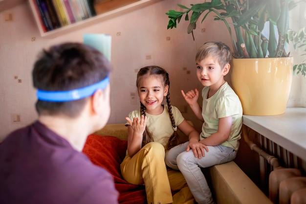 Glücklicher erwachsener vater, der mit seinen zwei kindern im häuslichen innenraum am brettspiel spielt, familienwerte tatsächlich, zu hause bleiben, leben während der quarantäne