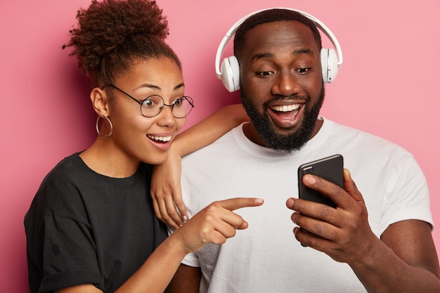 Glücklicher ethnischer freund-freund schaut fröhlich auf smartphone-gerät, zeigt auf anzeige, sieht lustiges video, durchsucht soziale netzwerke, hört musik in kopfhörern, verbringt freizeit mit moderner technologie