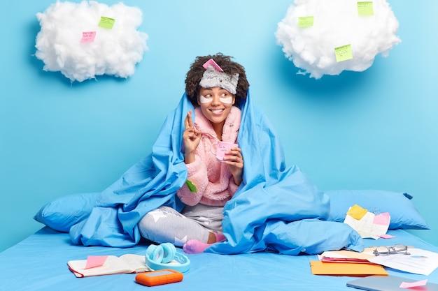 Glücklicher ethnischer student sitzt auf dem bett in der nachtwäsche, drückt die daumen und glaubt an viel glück
