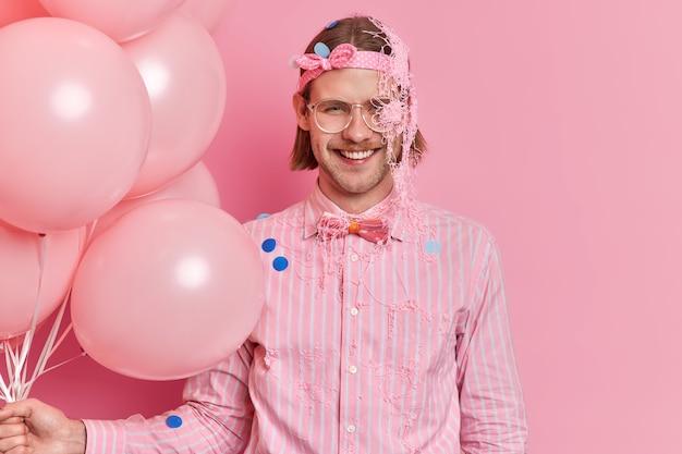 Glücklicher europäischer erwachsener mann trägt stirnband und gestreiftes hemd mit fliege, die durch serpentinenspray verschmiert wird, genießt partyfeier hält bündel von luftballons, die über rosa wand isoliert werden