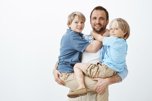Glücklicher europäischer vater, der zwei jungen auf händen hält und breit lächelt, erfreut ist und seine söhne liebt, vereinte und enge familie