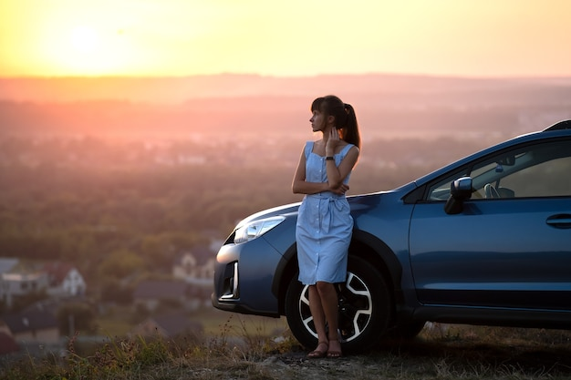Glücklicher fahrer der jungen frau im blauen kleid, der warmen sommerabend genießt, der neben ihrem auto steht. reise- und urlaubskonzept.