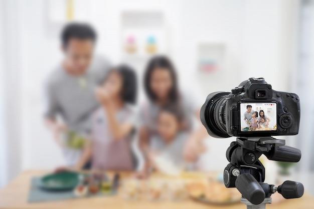 Glücklicher familienasiat, der eine vlog-videoblogger-digitalkamera mit dem kochen im küchenraum macht