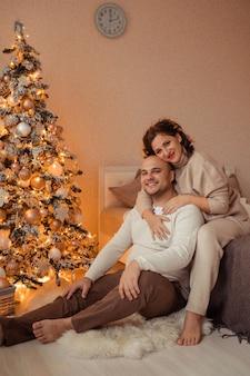 Glücklicher familienmann und ehefrau umarmen sich zu hause auf dem bett in der nähe des weihnachtsbaumes.