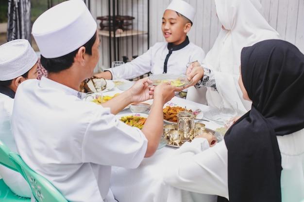 Glücklicher familienmuslim während der eid mubarak-feier durch gemeinsames essen zu hause