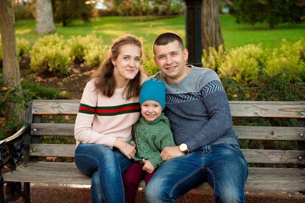 Glücklicher familienmuttervater und -baby auf herbst gehen in den park