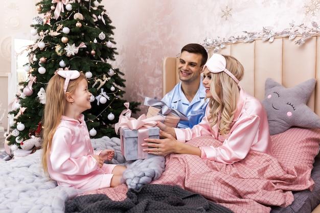 Glücklicher familienmuttervater und -kinder am weihnachtsmorgen im bett in den pyjamas