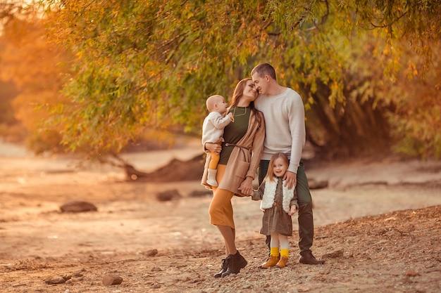 Glücklicher familienmuttervater und zwei töchter auf einem spaziergang in der natur im herbst