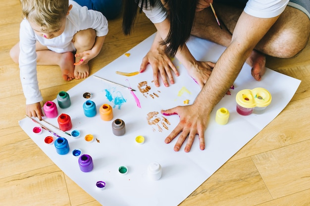 Glücklicher familiensohn mit eltern und einer katze, die ein plakat und miteinander mit farben malt